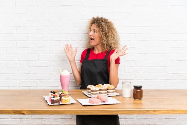 Giovane donna con un sacco di diverse mini torte in un tavolo con espressione facciale a sorpresa