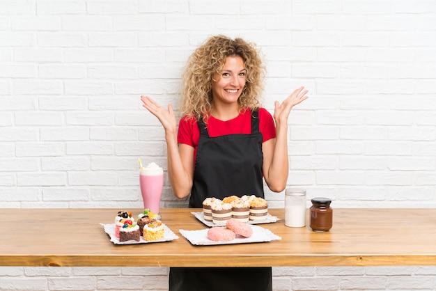 Giovane donna con un sacco di diverse mini torte in un tavolo con sorpresa espressione facciale