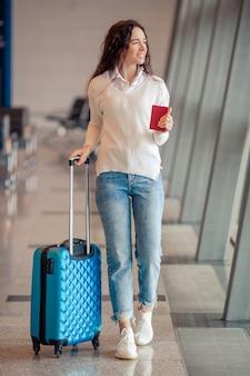 Giovane donna con bagagli in aeroporto internazionale. passeggero di linea aerea in un salotto dell'aeroporto in attesa di volo aereo