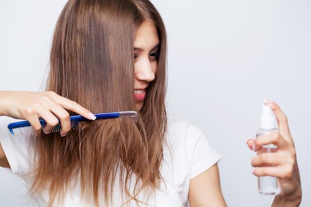 Giovane donna con capelli lussuosi applica balsamo per la cura dei capelli