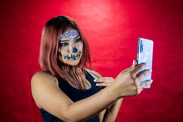 La giovane donna con il trucco per la festa di halloween si fa un selfie dal suo cellulare