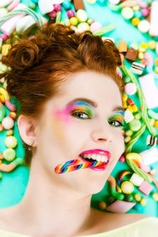 Giovane donna con molti dolci o caramelle malsane, ha un debole per i dolci