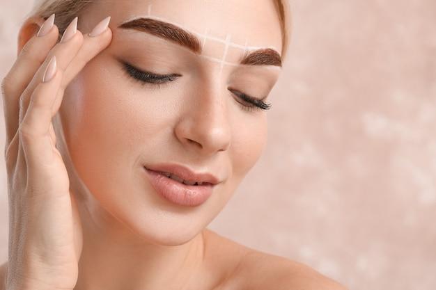 Giovane donna con la marcatura per la procedura di correzione delle sopracciglia sulla superficie del colore