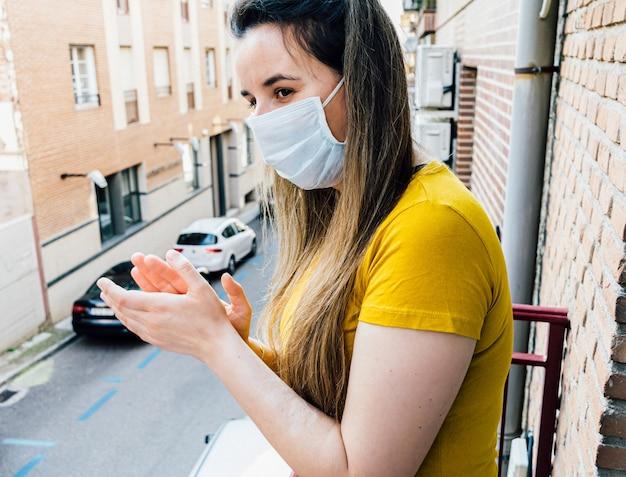 Giovane donna con maschera che applaude dalla terrazza al tramonto le persone che stanno combattendo contro il coronavirus