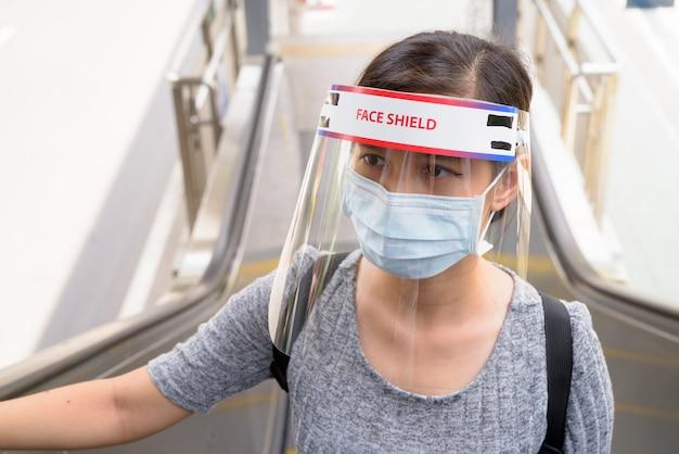 Giovane donna con maschera e visiera salendo la scala mobile