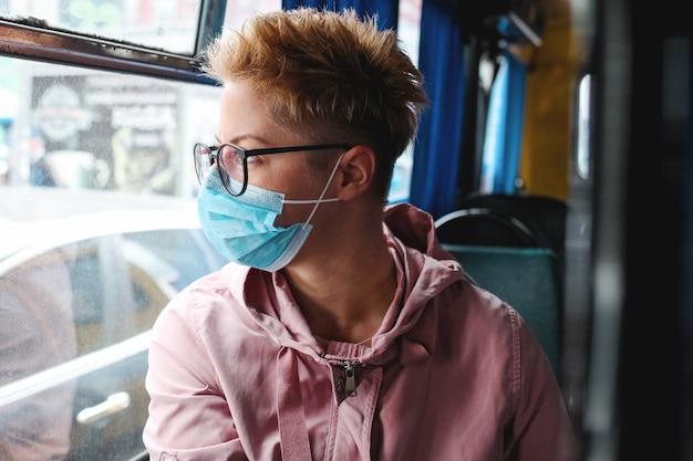 Giovane donna con maschera nel trasporto pubblico