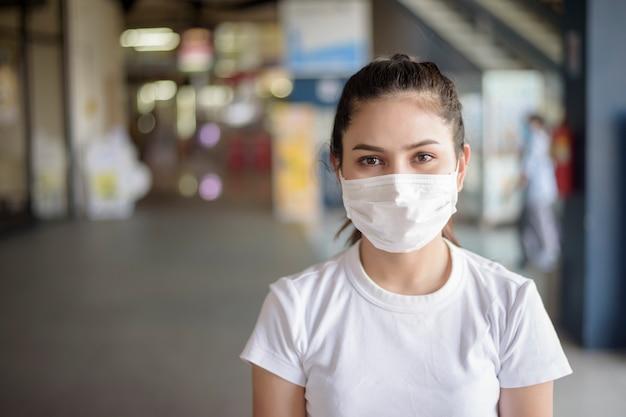 Giovane donna con la maschera che sta all'aperto