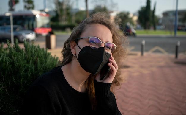 Giovane donna con maschera parlando al telefono seduto su una panchina in strada