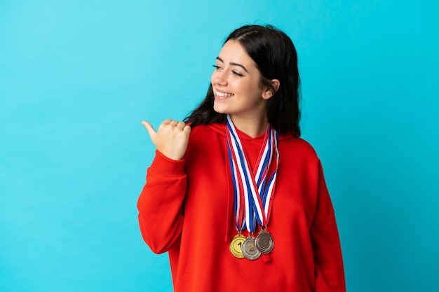 Giovane donna con medaglie isolate che punta di lato per presentare un prodotto