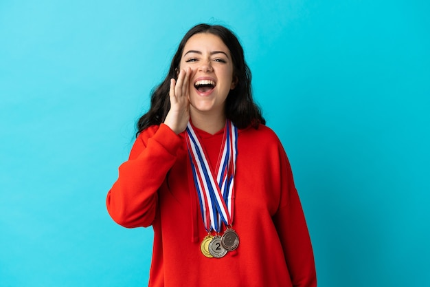 Giovane donna con medaglie isolato gridando con la bocca spalancata