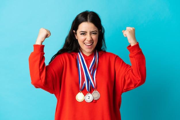 Giovane donna con medaglie isolato su bianco che celebra una vittoria