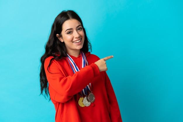Giovane donna con medaglie isolate su bianco che punta di lato per presentare un prodotto