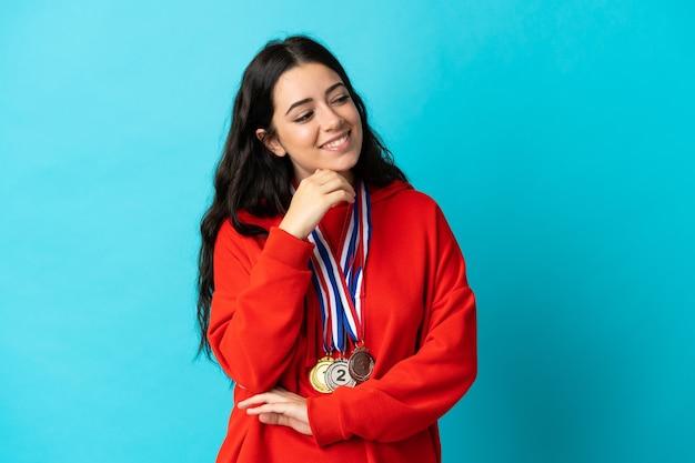 Giovane donna con medaglie isolato sul muro bianco guardando il lato