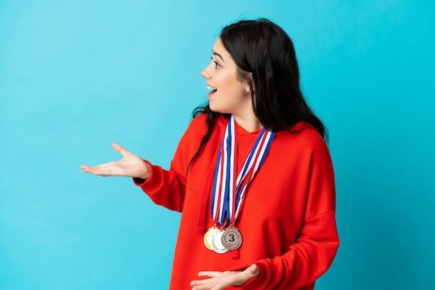Giovane donna con medaglie isolate con espressione facciale a sorpresa