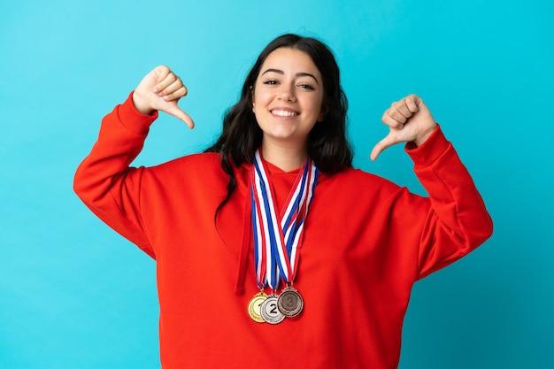 Giovane donna con medaglie su bianco orgoglioso e soddisfatto di sé