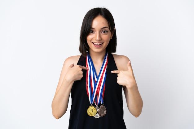 Giovane donna con medaglie su bianco con espressione facciale a sorpresa