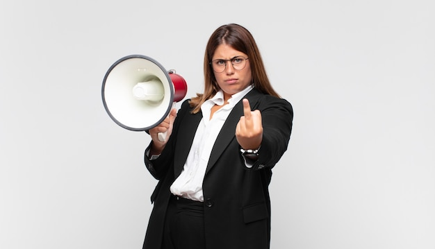 Giovane donna con un megafono che si sente arrabbiata, infastidita, ribelle e aggressiva, lancia il dito medio, reagisce