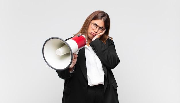Giovane donna con un megafono che si sente annoiata, frustrata e assonnata dopo un compito noioso, noioso e noioso, tenendo la faccia con la mano