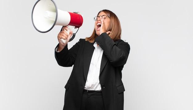 Giovane donna con un megafono che si sente felice, eccitato e positivo, dando un grande grido con le mani vicino alla bocca, chiamando