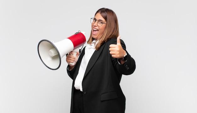 Giovane donna con un megafono che si sente orgogliosa, spensierata, sicura e felice, sorridendo positivamente con i pollici in su