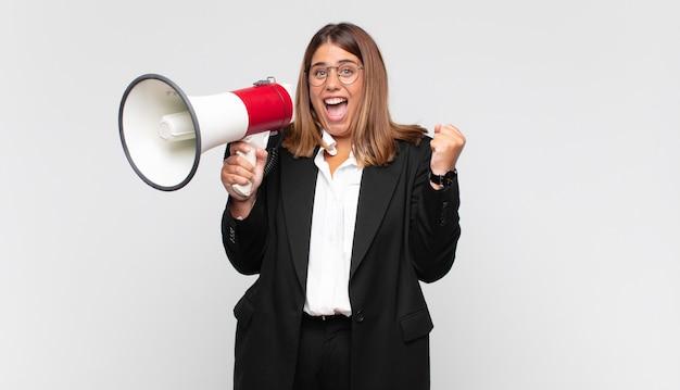 Giovane donna con un megafono che si sente scioccata, eccitata e felice, ride e celebra il successo, dicendo wow!