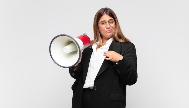 Giovane donna con un megafono che sembra arrogante, di successo, positiva e orgogliosa, indicando se stessa