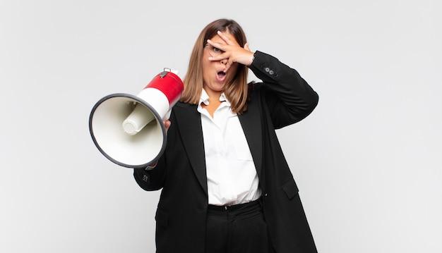 Giovane donna con un megafono che sembra scioccata, spaventata o terrorizzata, coprendo il viso con la mano e sbirciando tra le dita