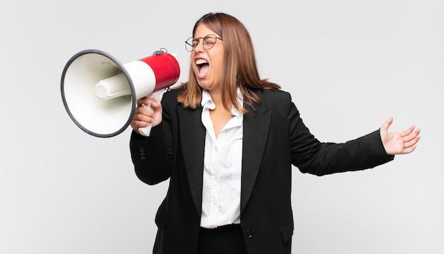 Giovane donna con un megafono che grida in modo aggressivo, sembra molto arrabbiato, frustrato, oltraggiato o infastidito, urlando no