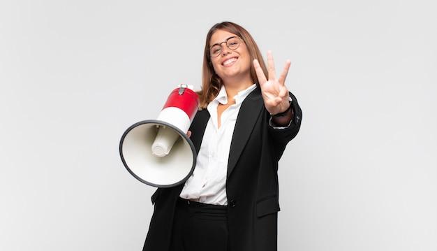 Giovane donna con un megafono sorridente e dall'aspetto amichevole, mostrando il numero tre o terzo con la mano in avanti, conto alla rovescia
