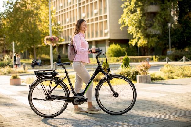 Giovane donna con trasporto urbano sostenibile pulito della bici elettrica elettrica moderna della città