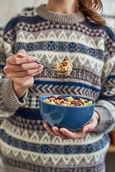 Giovane donna con uno spuntino o una colazione salutare in una ciotola di muesli al mattino