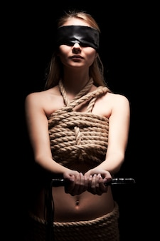 Giovane donna con il corpo nudo ricoperto di corde e gli occhi chiusi con uno straccio nero che tiene la sferza di cuoio nelle mani in camera oscura. giochi sessuali e pratica del concetto di bdsm
