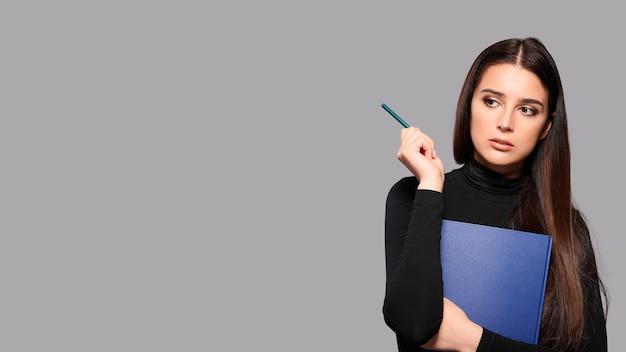 Giovane donna con blocco note e penna su sfondo grigio isolato