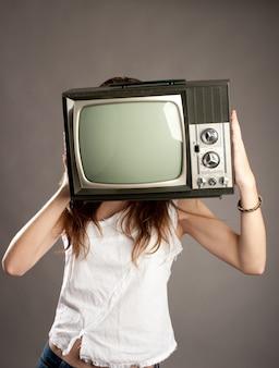 Giovane donna con la vecchia tv retrò