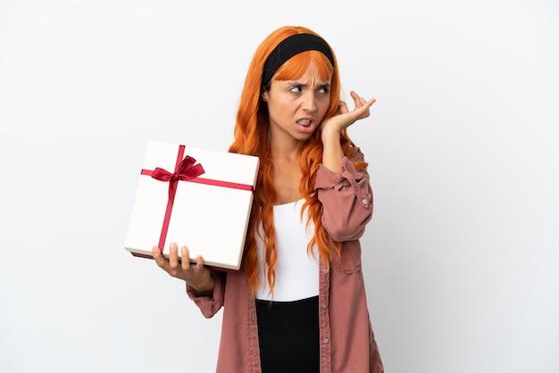 Giovane donna con i capelli arancioni che tiene un regalo isolato su sfondo bianco frustrato e che copre le orecchie