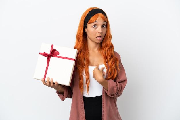 Giovane donna con i capelli arancioni che tiene un regalo isolato su sfondo bianco con espressione facciale a sorpresa