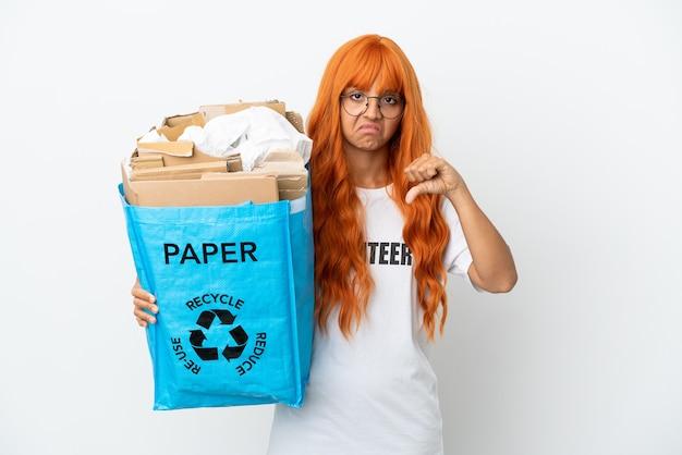 Giovane donna con i capelli arancioni che tiene in mano un sacchetto di riciclaggio pieno di carta da riciclare isolato su sfondo bianco che mostra il pollice verso il basso con espressione negativa
