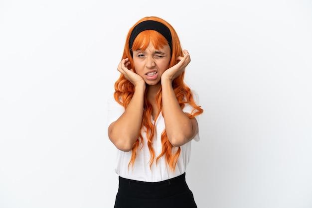 Giovane donna con i capelli arancioni isolati su sfondo bianco frustrata e che copre le orecchie