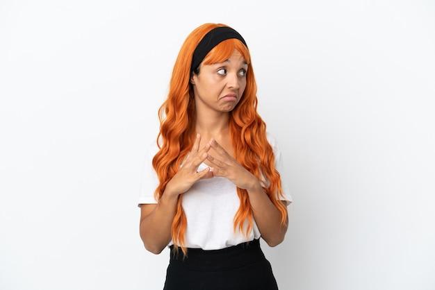 Giovane donna con i capelli arancioni isolata su sfondo bianco che trama qualcosa