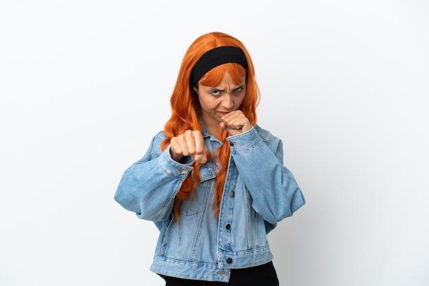 Giovane donna con i capelli arancioni isolata su sfondo bianco con gesto di combattimento