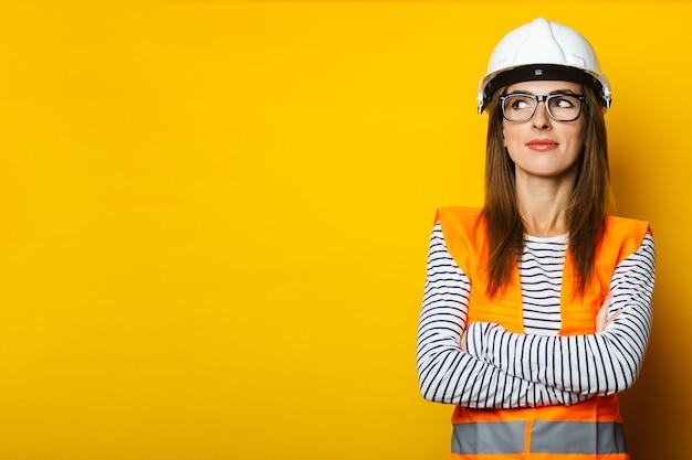 Giovane donna con un viso pensieroso in un giubbotto e un elmetto su uno sfondo giallo. concetto di costruzione, nuova costruzione. bandiera.