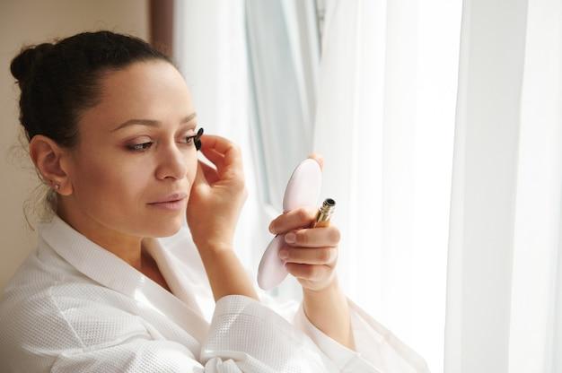 Giovane donna con un trucco perfetto che applica il mascara alle ciglia, guardando il piccolo specchio cosmetico mentre si trova davanti alla finestra