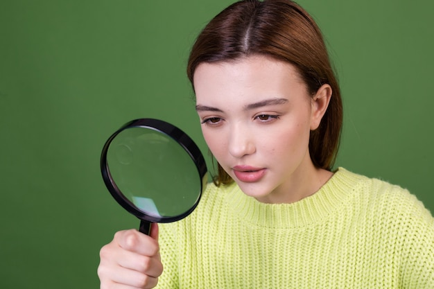 Giovane donna con grandi labbra marroni di trucco naturale perfetto in maglione casuale sulla parete verde con la ricerca della lente d'ingrandimento