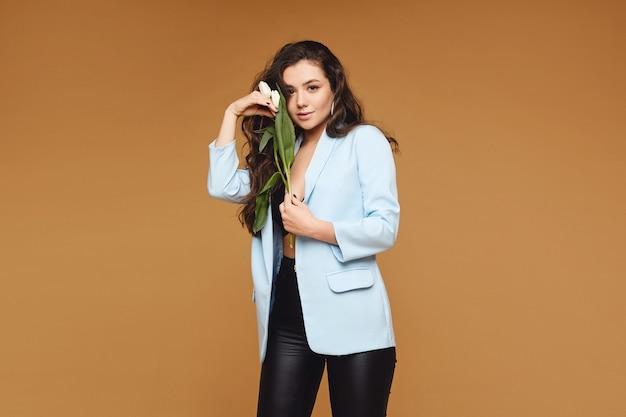 Giovane donna con il corpo perfetto sottile in posa con i fiori del tulipano sopra il muro beige, isolato con lo spazio della copia per testo e pubblicità