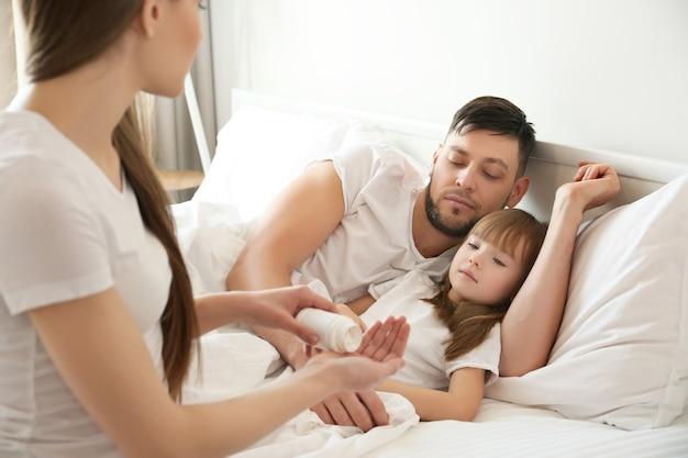 Giovane donna con pillole per la figlia malata e il marito a casa
