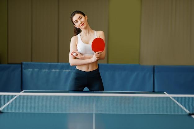 Giovane donna con la racchetta da ping pong al tavolo