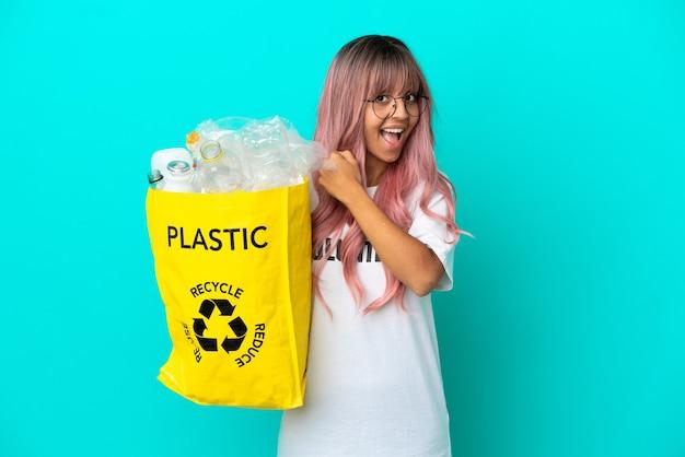 Giovane donna con i capelli rosa che tiene una borsa piena di bottiglie di plastica da riciclare isolata su sfondo blu che celebra una vittoria