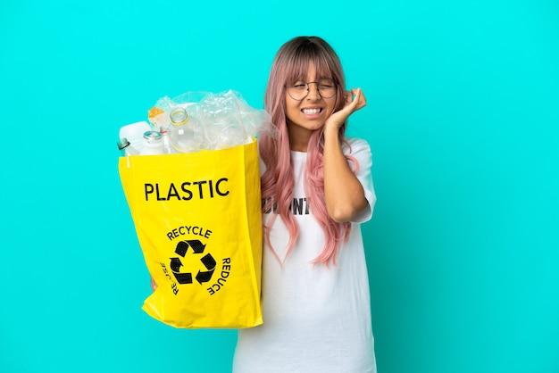 Giovane donna con i capelli rosa che tiene una borsa piena di bottiglie di plastica da riciclare isolata su sfondo blu frustrata e che copre le orecchie