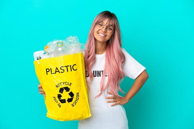 Giovane donna con i capelli rosa in possesso di un sacchetto pieno di bottiglie di plastica da riciclare isolato su sfondo blu in posa con le braccia all'anca e sorridente