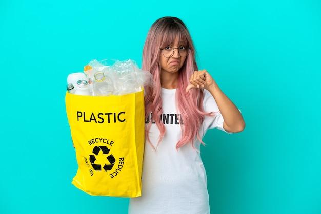 Giovane donna con i capelli rosa in possesso di un sacchetto pieno di bottiglie di plastica da riciclare isolato su sfondo blu che mostra il pollice verso il basso con espressione negativa